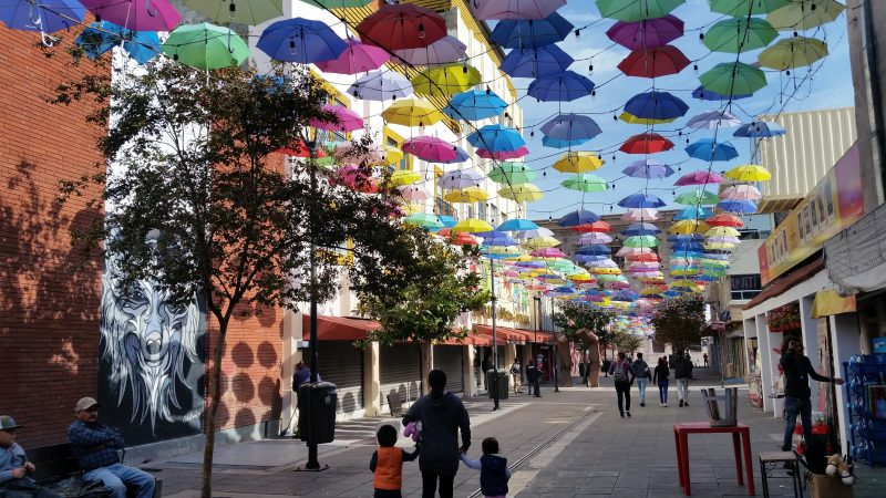Hundreds of multi-colored umbrellas hanging above a pedestrianized street in Chihuahua, Mexico.