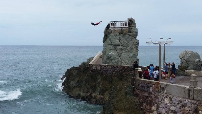 A small crowd of people watching a man dive off a cliff into the ocean in Mazatlan, Mexico.