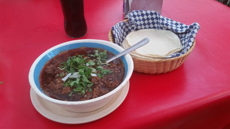 A bowl of birria stew on a red table, accompanied by a basket of corn tortillas.