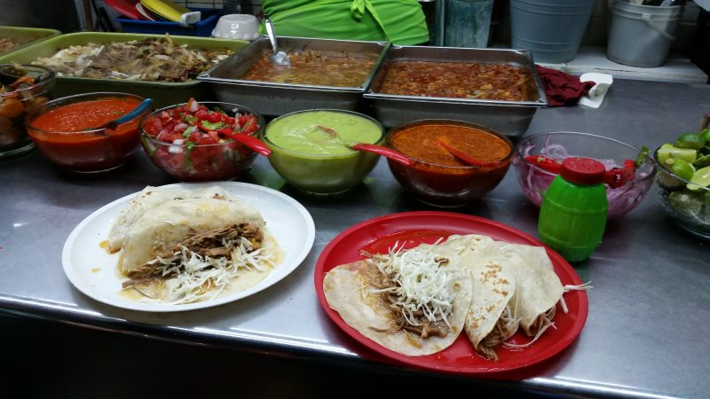 Two plates of tacos with small bowls of salsa and some trays of shredded meat in the background.