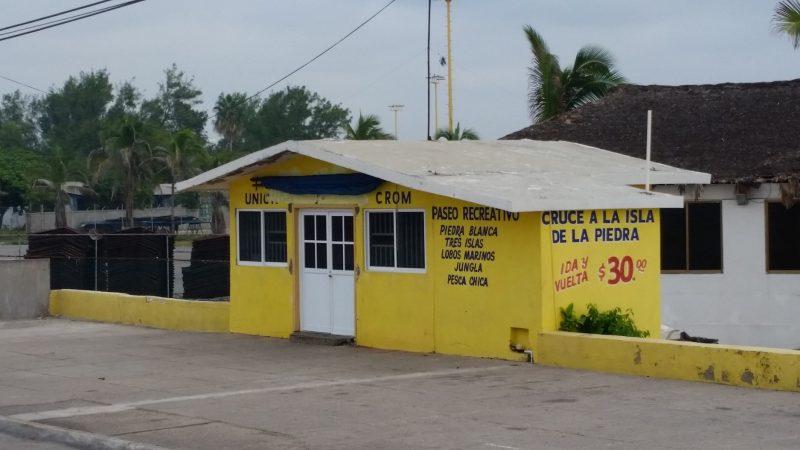 A yellow concrete building in Mazatlan, Mexico selling tickets for tour boats to Isla de la Piedra.