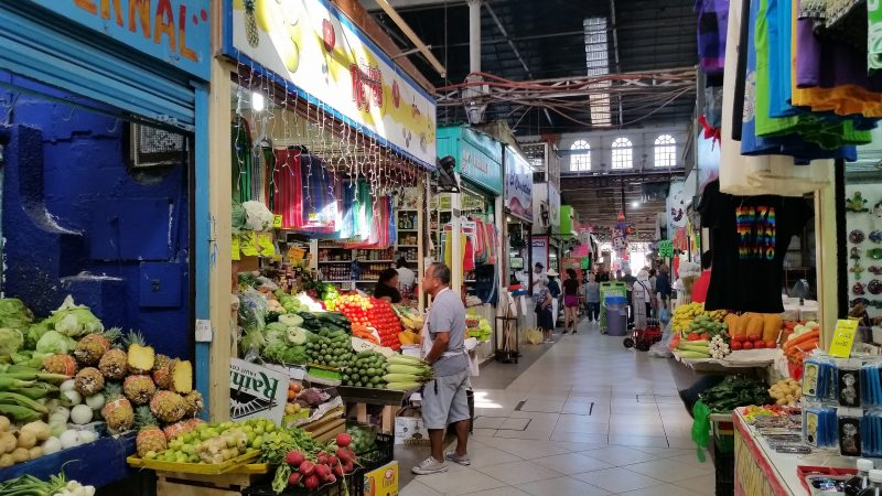 A man standing in front of a stall selling a variety of colorful fruits and vegetables at Mercado Pino Suarez in Mazatlan, Mexico.
