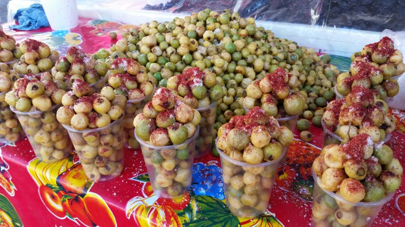 Nance fruit sprinkled with salt and red chili powder being sold from a street food vendor in Mexico.