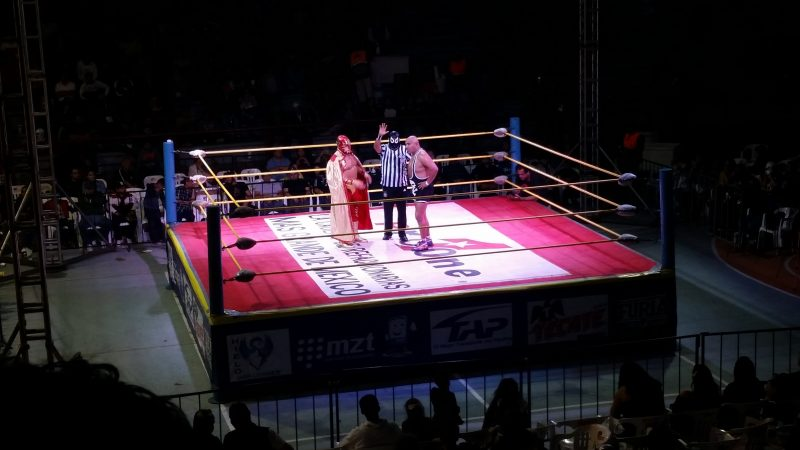 Two masked wrestlers in a ring and one unmasked wrestler at a venue in Mazatlan, Mexico.