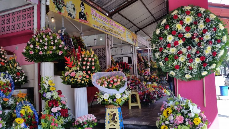 A few market stalls displaying colorful, assorted flower arrangements in Mazatlan.