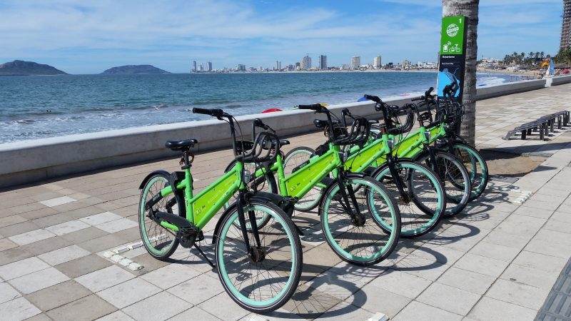 A row of green Vbikes on the malecon in Mazatlan with crashing waves and several islands off the coast visible in the background.