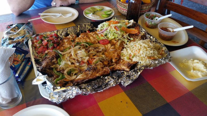 A whole fish grilled and served Zarandeado-style at one of the famous beachfront seafood palapa restaurants in Mazatlan, Mexico.