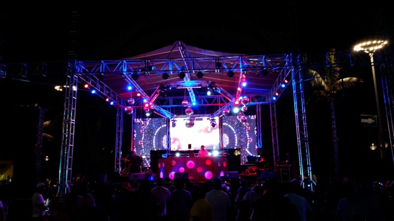 A nighttime view of people surrounding of a colorfully-lit stage featuring a DJ.