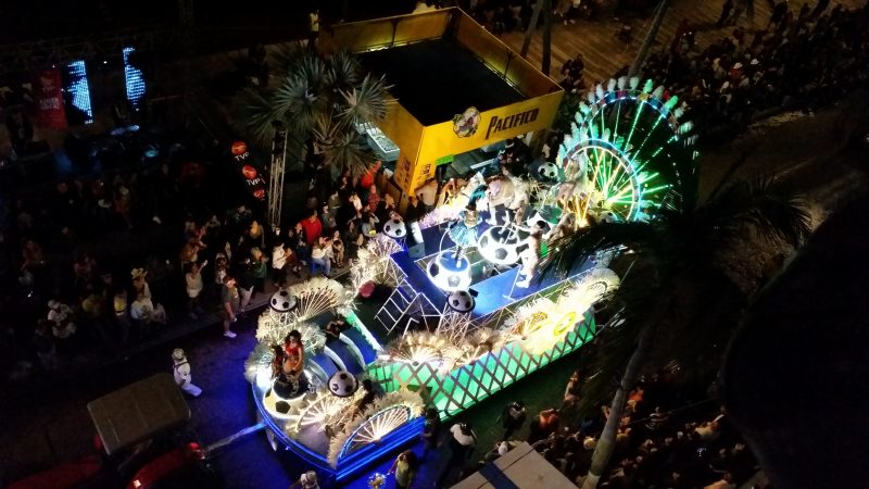 A colorful Mardi Gras parade float at night as viewed from above.