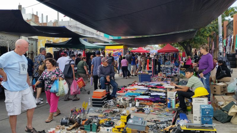 A flea market in Maztlan, Mexico with a man in a blue shirt and white shorts looking at a display of used tools with market-goers walking past.