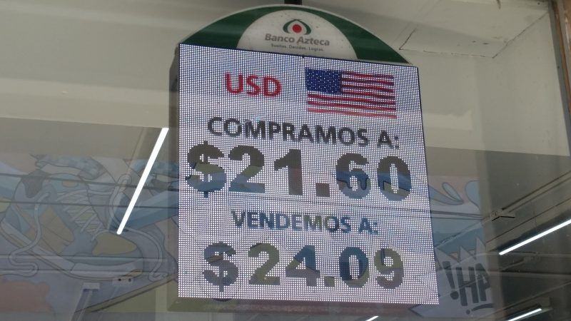 A LED sign from Banco Azteca advertising currency exchange rates for U.S. dollars; getting good rates from money exchange is one best travel tips in Mexico.