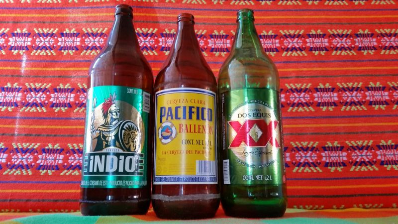 Three of the famous 1.2 liter beer bottles of Pacifico, Indio and Dos Equis; knowing where and exactly how to get these is one of the best travel tips in Mexico.