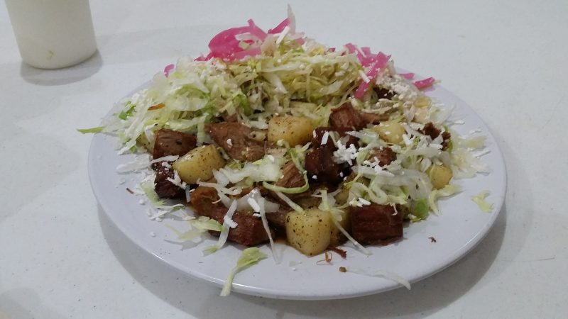 A white plate on a white table-top, piled up with cubes of beef and potatoes from one of Mazatlan's traditional cenaduria-style restaurants.