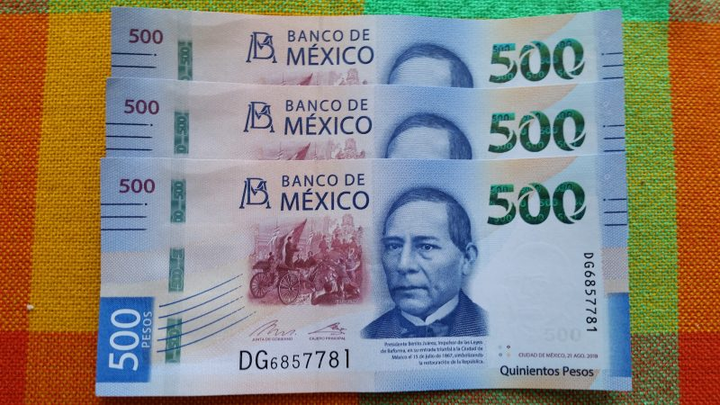A total of three 500 Mexican Peso bills on a brightly-colored tablecloth..