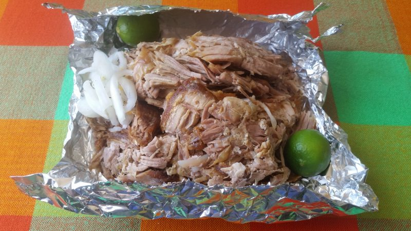 A platter of carnitas, or shredded pork, on a large piece of aluminum foil with limes and onions garnishing it.