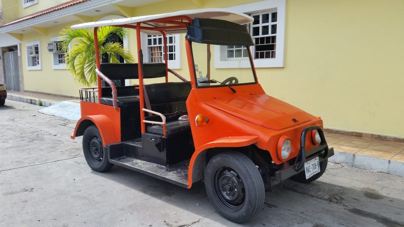 A unique orange pulmonia parked in front of a yellow building.