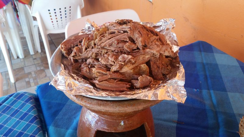 A serving of tender, shredded lamb served on a plate atop a terracotta chafing dish at a popular restaurant in Mazatlan, Mexico.