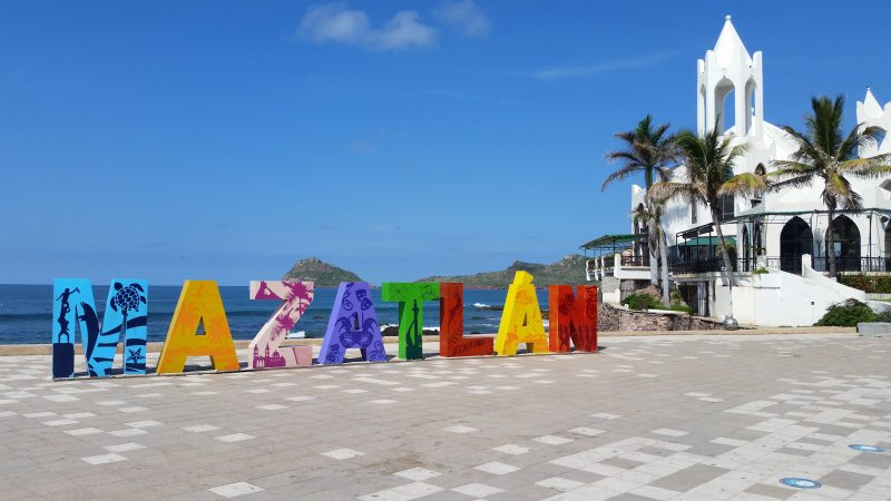 "A collection of large colorful letters spelling out ""Mazatlan"" with the famous Valentino's building and the ocean in the background."