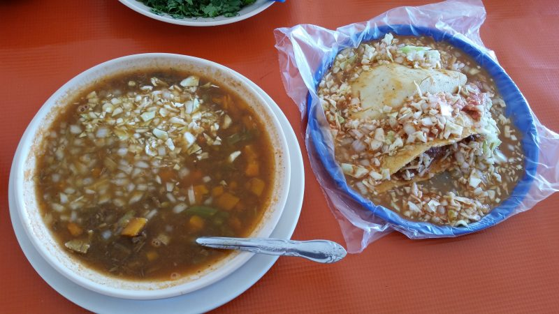 A bowl of caguamanta soup and a plate with two smoked marlin tacos, both local specialties found at authentic seafood restaurants in Mazatlan, Mexico.