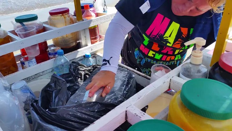 A woman scraping a specially-designed tool across a block of ice; these are known as raspados in Mexico and are sold as a snack with fruit syrups added for flavor.