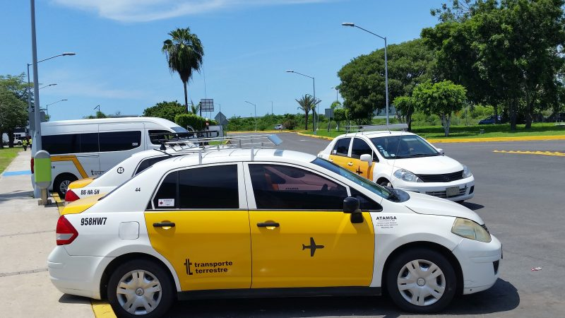 A unionized yellow and white taxi at General Rafael Buelna International Airport in Mazatlan, Mexico.