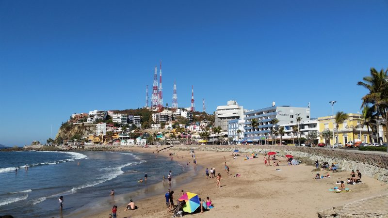 A view of people swimming, several oceanfront restaurants and the Hotel Belmar at Playa Olas Altas in Mazatlan, Mexico.