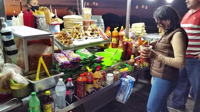 A street food vendor along the Mazatlan Malecon with a customer adding condiments to her snack.