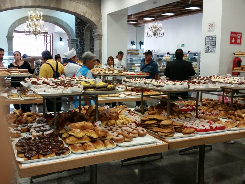 A bakery in Mexico City filled with workers and many customers picking from a selection of pastries.
