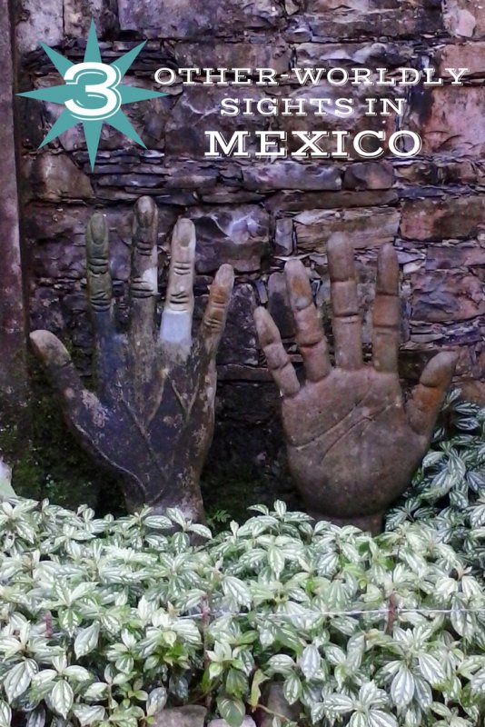 Two concrete statues of right hands in a bed of green plants.