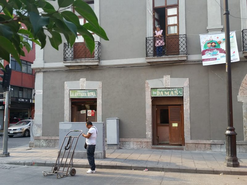 A woman standing on a balcony looking down on the street at a man with a cart.