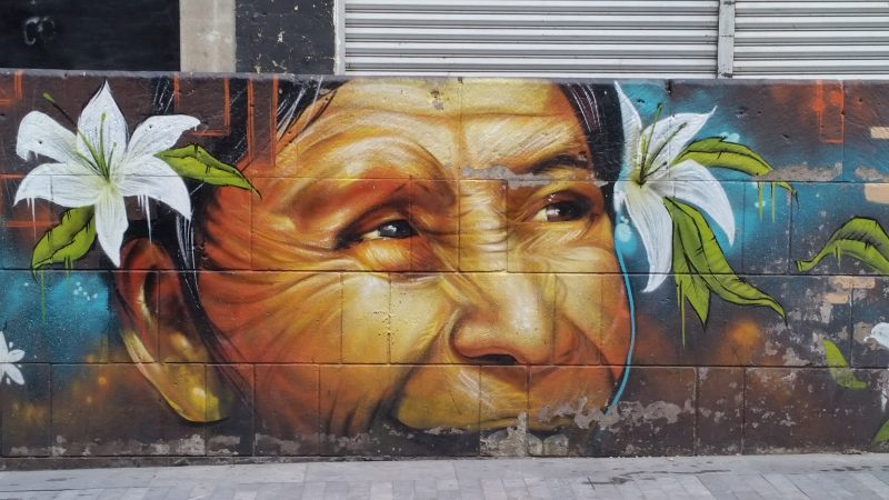 An example of colorful urban artwork on of an old lad's face in the streets of Mexico City.
