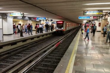People standing on a platform of a subway station in Mexico City as a train is pulling in.