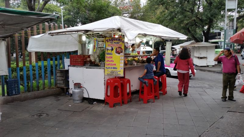 A white taco cart on the sidewalk with several red plastic stools
