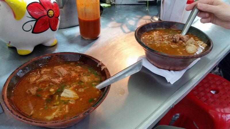 Two bowls of birria stew with spoons.