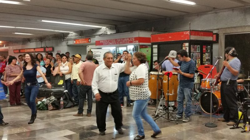 People dancing in the interior of a Mexico City Metro Station.
