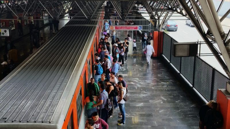 People on a platform boarding an orange train in Mexico City.