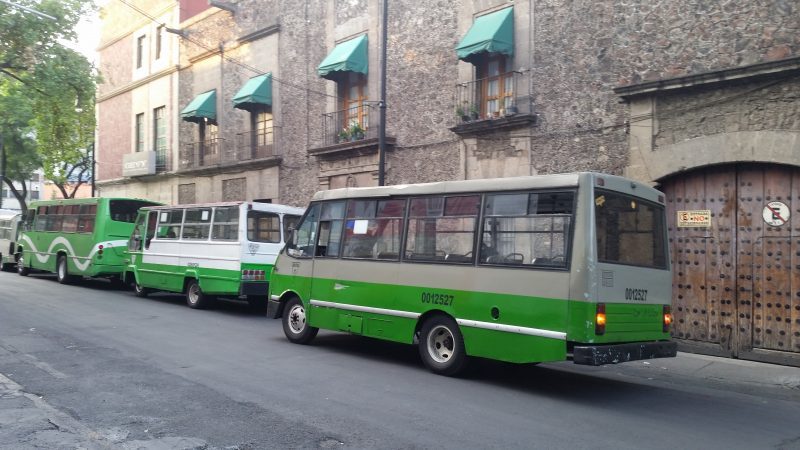 Green buses parked in front of an old stone building.