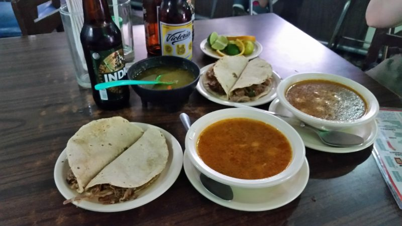 Two bowls of soup and a plate of two tacos with several bottles of beer, served as botanas in a cantina in Mexico City.