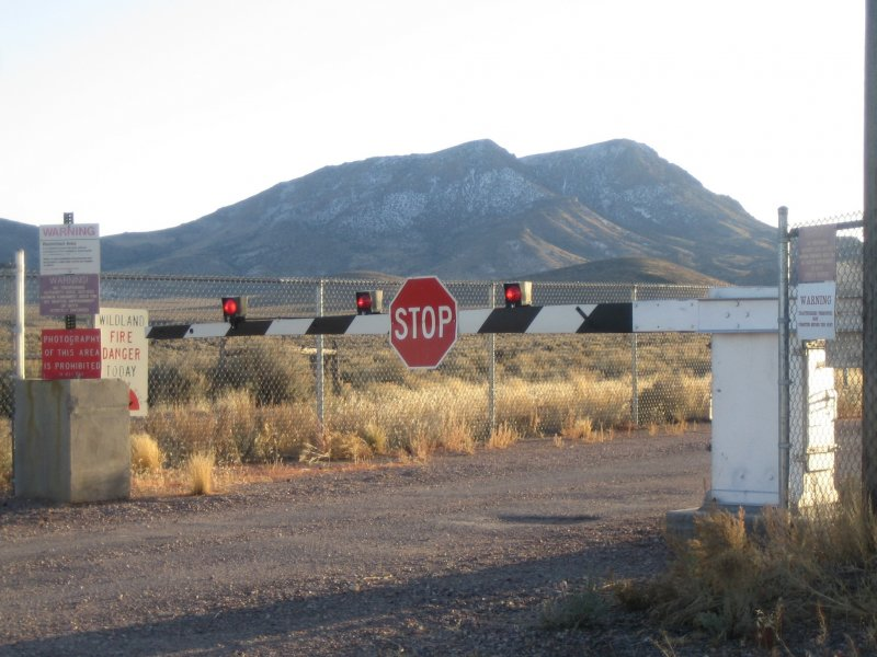 A gate with a stop sign on it going across a dirt road with a mountain in the background.