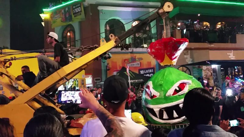A tow truck hauling an effigy of a green head through a crowd of revelers at Carnaval in Mazatlan.