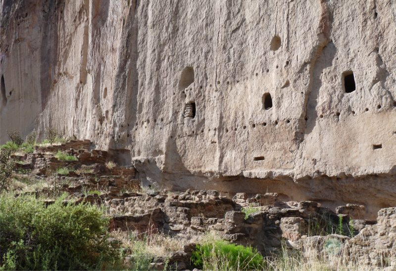 Adobe ruins built against a sheer cliff base with holes carved into it.