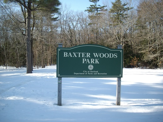 A sign for Baxter Woods Park in Portland, Maine surrounded by tress and snow.
