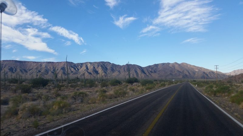 A road in the desert of Baja California with mountains in the background.