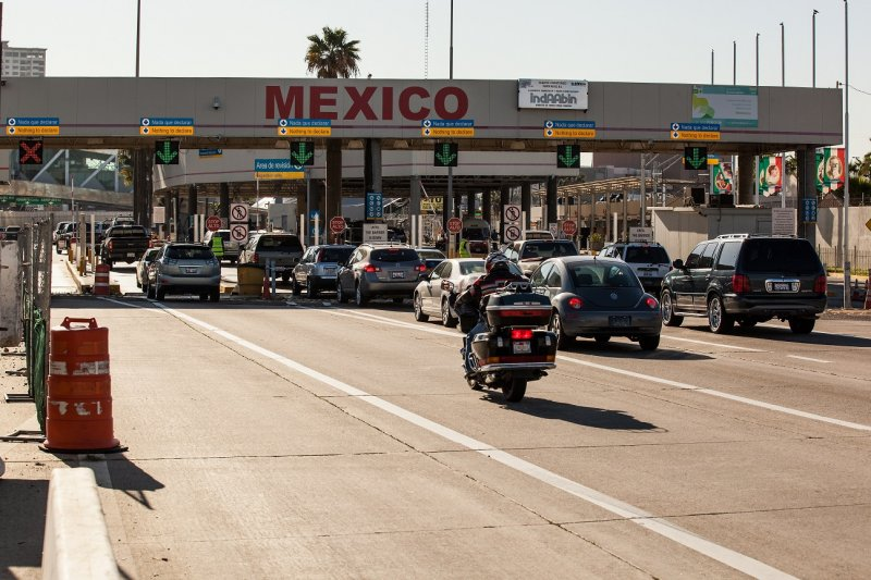 About a dozen vehicles approaching a border crossing into Mexico.