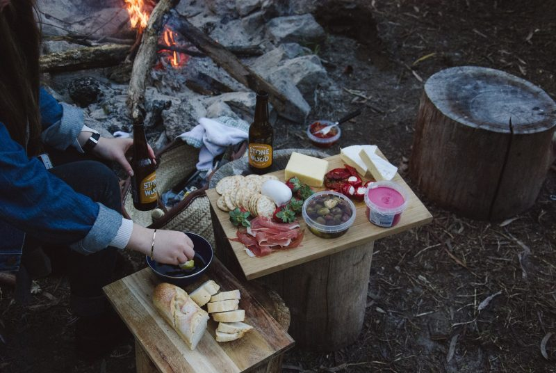 Charcuterie board filled with meats and cheese in front of a campfire.