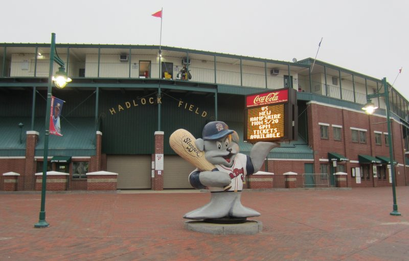 The entrance to Hadlock Field in Portland Maine with a mascot in front holding a light-up sign.