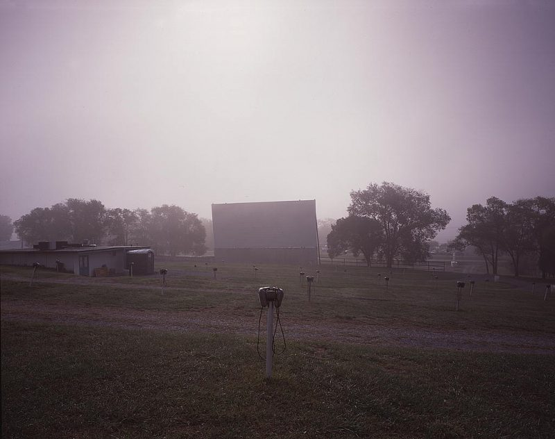 A drive-in movie screen through the fog of an early morning.