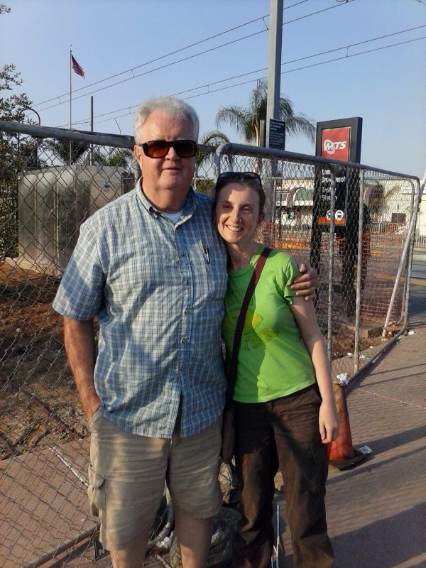 Man and woman in front of a chain link fence.