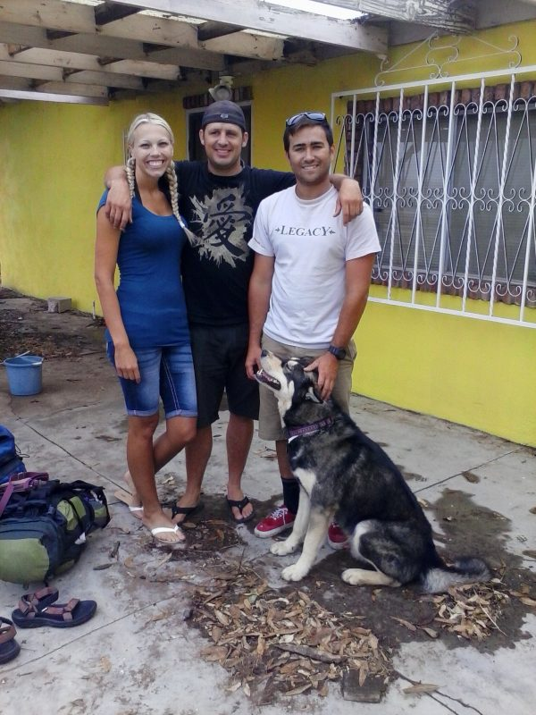 Three people and a dog in front of a yellow house.