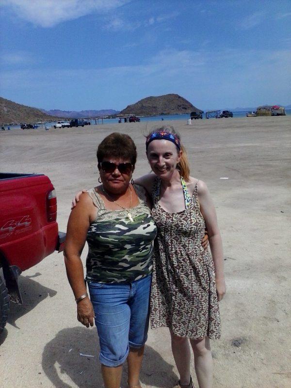 Two women standing on Santispac Beach.